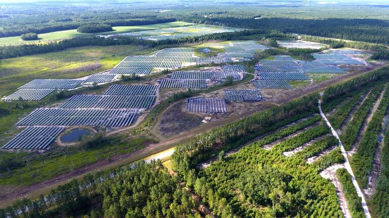 tech - high aerial view of solar panels and trees