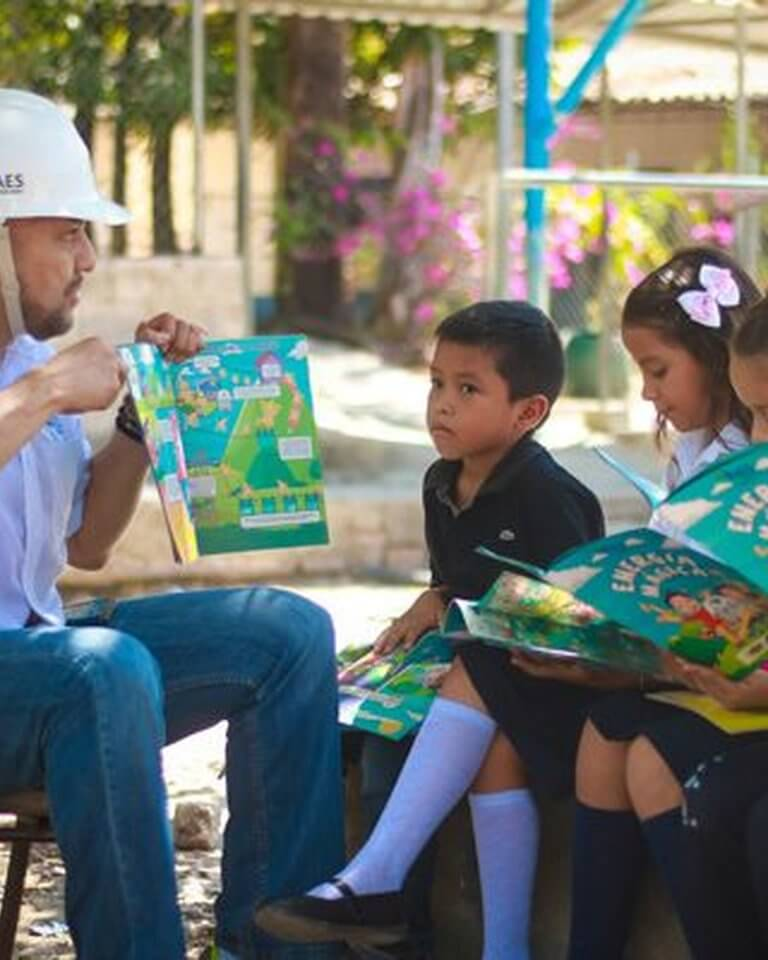 Energy worker reading storybook to children.