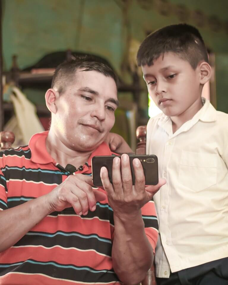 Man sharing content on his phone with a boy