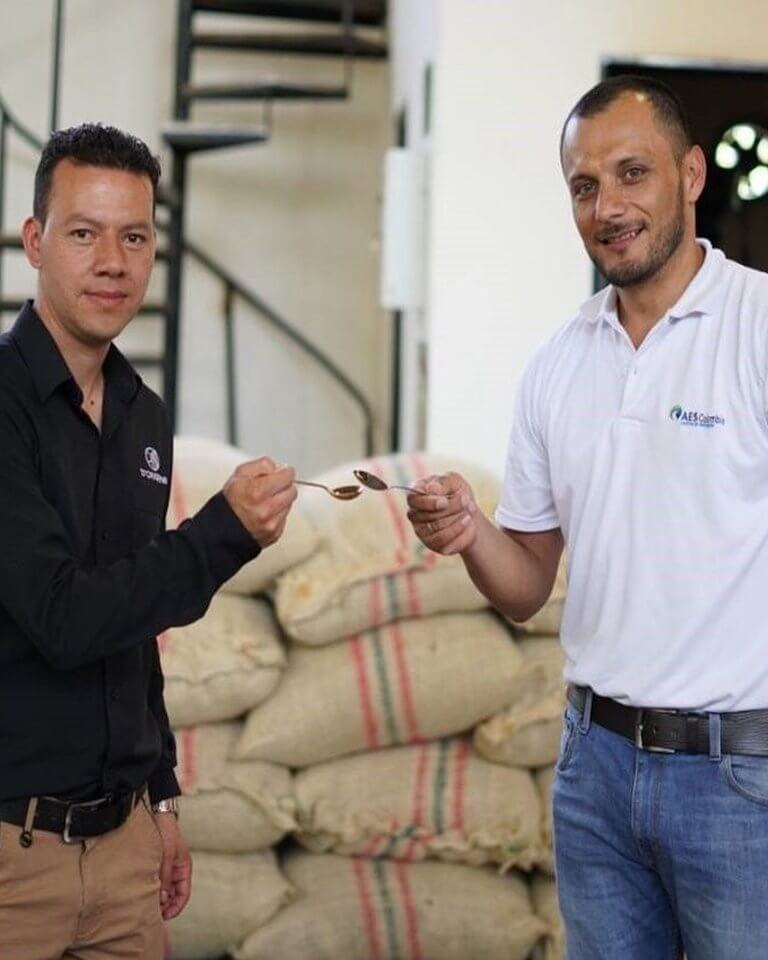 two men standing with coffee bags