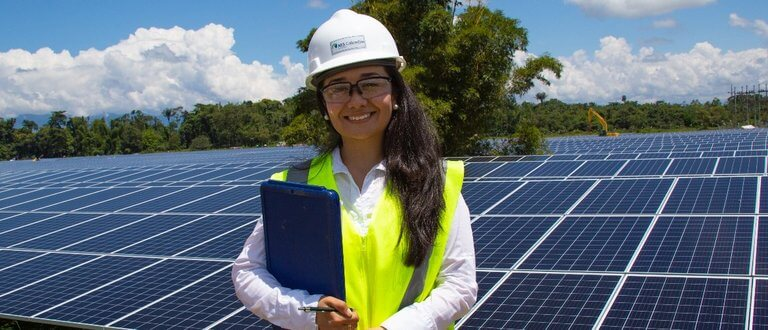 tech - smiling woman in hard hat with clip board and solar panels