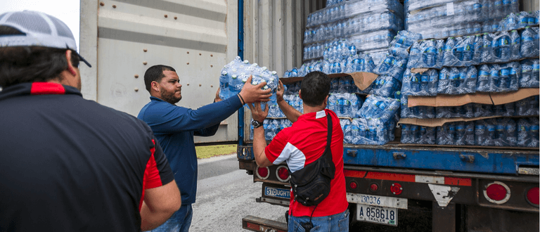 Hurricane Relief Workers Sharing Water Bottles